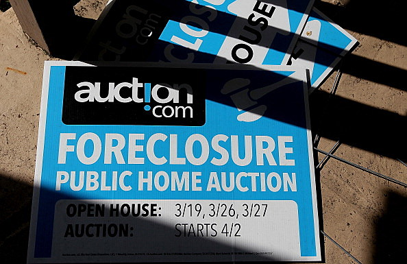 Foreclosure signs sit on the porch of a foreclosed hom