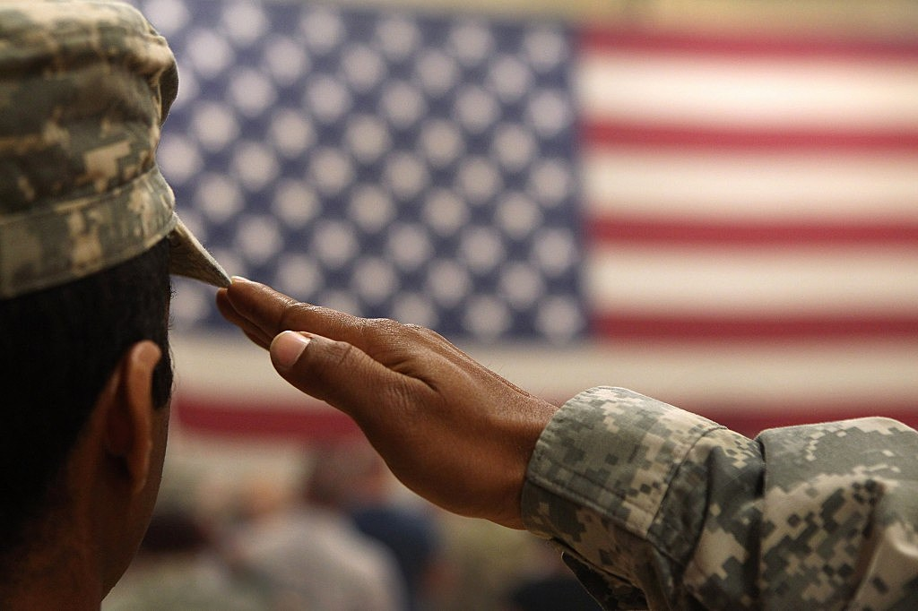 A soldier salutes the flag during a welcome home ceremony for troops