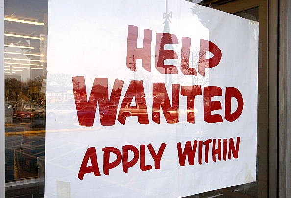 """Help Wanted Apply Within"" is seen hanging in a window"