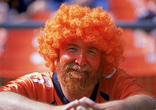 A fan of the Denver Bronocs wears a orange curley wig as he smiles